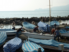 Men cover the boats to protect them from the winter in Chiavari